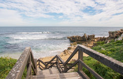 Walkway to the Beach: Penguin Island. Indian Ocean seascape at Penguin Island with boardwalk, remote beach and limestone rock under a blue sky with clouds in Stock Photos