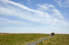 Walkway to heaven. An elderly couple walking on a path to a big sky Stock Photography