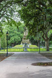 Walkway to Lafayette. Old oak trees in Forsythe park in the southern United States with statue of Lafayette Stock Images