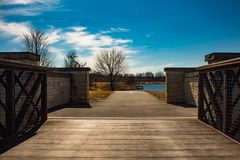 Walkway to the lake through bridge and gate in park Libertyville illinois royalty free stock photo