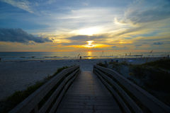 Walkway to ocean. Sunset on the Gulf Of Mexico beach golden ball with a few clouds over the ocean. Wooden walkway to ocean with sea grass and sunset Stock Images