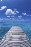 Walkway to paradise island polynesia. A wooden walkway over the sea to a paradise tropical island polynesia Royalty Free Stock Image