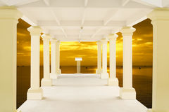 Walkway in tunnel structure and blurry sunset over the sea in background Royalty Free Stock Images