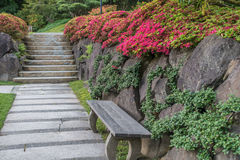 Walkway, Wall And Flowers 4. A walkway is in front of a rock wall with flowers at a seattle garden Stock Photo