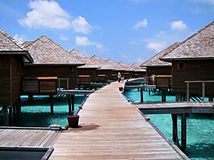 Walkway with water bungalows on both sides in Maldives. Walkway with water bungalows on both sides and with a couple of tourists strolling around, in Maldives Royalty Free Stock Images