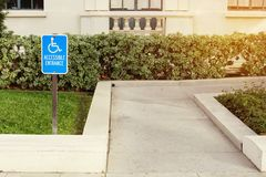 A Walkway Wheelchair Accessible Sign for Handicap Disabled. View of a disabled person walk way with a blue handicap sign royalty free stock photo
