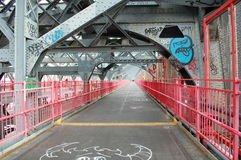 Walkway of Williamsburg Bridge in New York City. The walkway of the Williamsburg Bridge between Manhattan and Brooklyn in New York City with iconic pink railings Stock Images