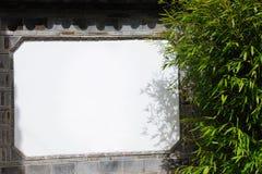 Wall. White board on a brick wall near the bamboo Stock Photos