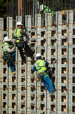 On the Wall. Four construction workers high up on the wall of a new building royalty free stock image