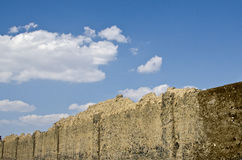 Wall. Blue sky behind the wall of mud Royalty Free Stock Photos