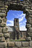 Through the Wall. St Paul's church in Jarrow. Once home of the Venerable St Bede. The stonework in the foreground is part of what remains of the monastery Royalty Free Stock Images