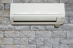 Wall air conditioning hanging on a brick wall. Stock Images