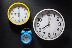 Wall and alarm clock at black background Royalty Free Stock Photos