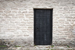 Wall of an ancient castle with black metal door Stock Photos