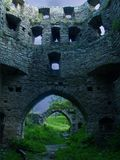 The wall of an ancient stone fortress: a masonry with empty window apertures, at the bottom of an arch among which the bright gree Royalty Free Stock Image