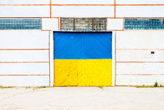 Wall of ancient warehouse with door in ukrainian flag colors - blue and yellow. Ukrainian flag on background of old locked doors Stock Photos