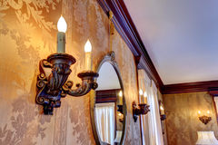 Wall with antique candelabrums and mirror. Wall in luxury house. View of antique candelabrum and mirror stock photos