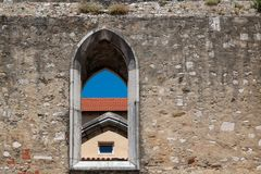 Wall with an arc window, Lisbon, Portugal. Old wall made of stones with and arc window. Another building in the background. Clear blue sky. Lisbon, Portugal Stock Photo