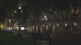 Wall with arches illuminated at night, lights of cafes across deserted street. Stock footage stock video