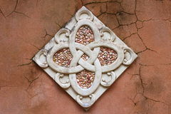 Wall Art. A rustic looking garden wall made beautiful by a carved stone and mosaic patterned decoration Stock Images