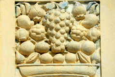 Wall art stucco work of fruits in basket designs on exteriors of 200 year old temple Stock Photos