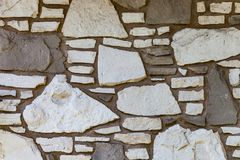Wall background with irregular sized white and brown stones.  royalty free stock photography
