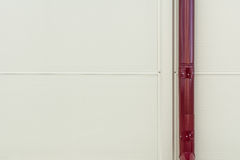 Wall background from ribbed metal profile and red drainage pipe Stock Image