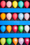 Wall of Balloons. A blue wall case with colorful balloons. Photo is of a boardwalk arcade game. Only the wall case and balloons are shown Royalty Free Stock Photos