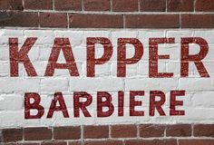 Wall with barber shop sign written in Dutch and Italian Stock Photos