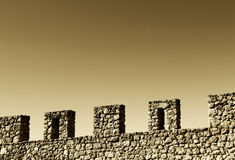 Wall with battlements, space for text, sepia hue. A composition with an ancient stone wall with battlements, from the medieval castle of mussomeli, sicily, a Stock Photo