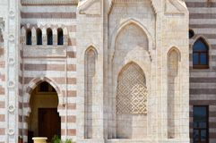A wall with a beautiful texture of a Muslim Islamic Arab mosque made of white brick architecture with arches, tall towers, domes a royalty free stock image