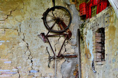 Wall bicycle. Old and rusty bicycle on the wall of an old abandoned house in northern italy Stock Image