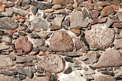Wall of big stones and broken bricks. Old wall made of big stones and broken bricks. Vintage rough blocks surface background royalty free stock photography
