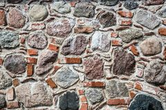 Wall of big stones and broken bricks. Old wall made of big stones and broken bricks. Vintage rough blocks surface background royalty free stock images