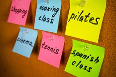 Board with colorful stickers reminders activities and hobbies: pilates Spanish class cooking class tennis shopping cinema. Wall board on the room of girl or lady royalty free stock photography