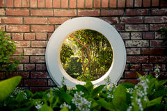 Wall brick and circle white window over green bush in the park with the sunlight. Authentic tree bush leaves wallpaper detail patt Royalty Free Stock Photography