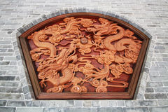 Wall brick stone sculpture wood crafting dragon miracle ball. Wall brick stone sculpture with wood crafting of two dragon and glass miracle ball Royalty Free Stock Photos