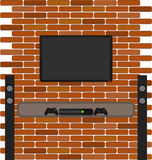 Wall brick with tv and game console hanging on it Stock Image
