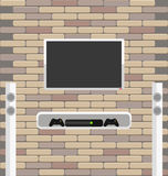 Wall brick with tv and game console hanging on it Royalty Free Stock Image