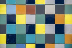 Wall of bright multi-colored yellow, blue, white, gray square ceramic tiles. rough surface texture. A wall of bright multi-colored yellow, blue, white, gray royalty free stock image