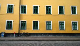 Wall bright yellow house with lots of beautiful Windows. To the wall leaning the bike. Near a small post royalty free stock photos