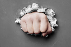 Wall is broken through by a fist Royalty Free Stock Photo