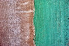 Wall with brown and bright green turquoise shabby paint on white background, stripe divide on two halves, grunge texture. Background stock images