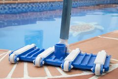Wall Brush and Leaf Skimmer Maintenance Tools on Deck Beside Swimming Pool. Piscina royalty free stock image