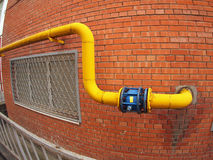 Wall of a building with a gas pipe and a large valve. Wall of a building with a yellow gas pipe and a large valve with wide angle fisheye view royalty free stock photography