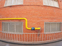 Wall of a building with a gas pipe and windows. Wall of a building with a yellow gas pipe and windows with wide angle fisheye stock photo
