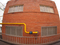 Wall of a building with a gas pipe and windows. Wall of a building with a yellow gas pipe and windows with wide angle fisheye view stock photography