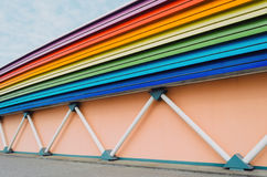 Wall of the building, supports in the form of pipes, and roofs illuminated in the form of a rainbow. Stock Photo