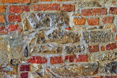 The wall built of irregular stones and bricks background. Texture of old stonework. Space for text. The concept of reliability Stock Photos