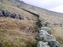 Wall built up a hill. Top of wall is very well know, hole in the wall - leading to Striding Edge, Lake District Stock Photography